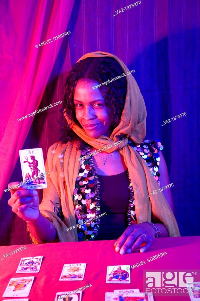 Stock Photo: Female Tarot Card reader holding 'Le Diable' Crad.