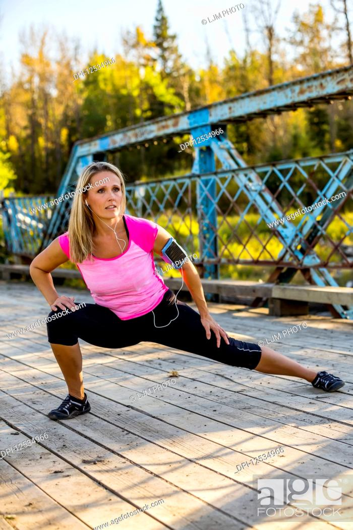 Photo de stock: An attractive middle-aged woman listens to music on her smart phone and pauses to stretch out her legs on a bridge during a run on a beautiful warm fall evening.