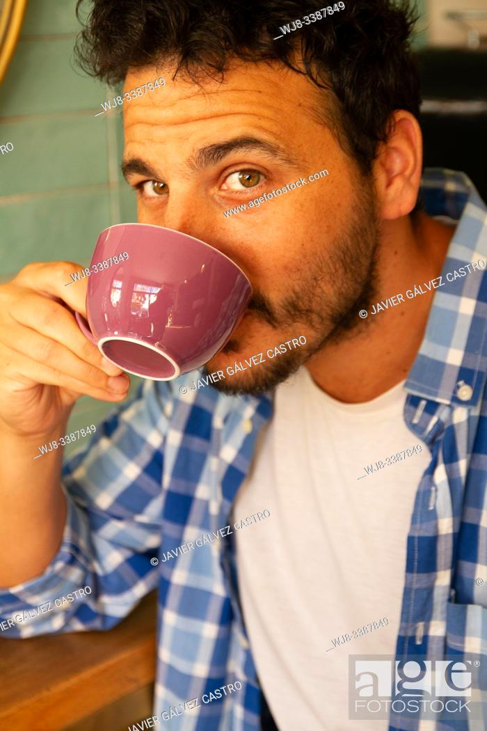Stock Photo: Portrait of a young man drinking coffee.