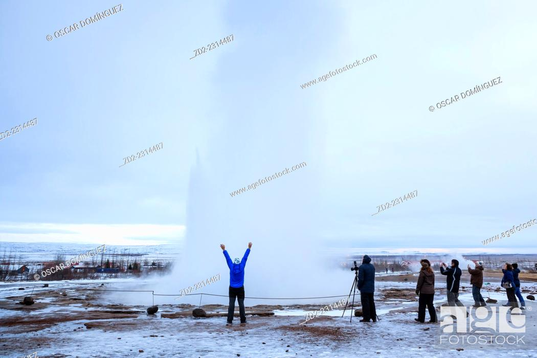 Stock Photo: Visitors watching the famous Strokkur geyser wich erupts about every 4–8 minutes. Geysir. Haukadalur. Iceland.