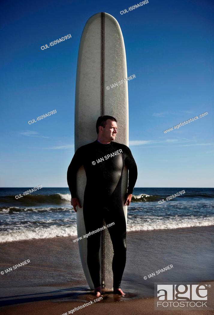 Stock Photo: Portrait of mature man standing with tall surfboard on beach.