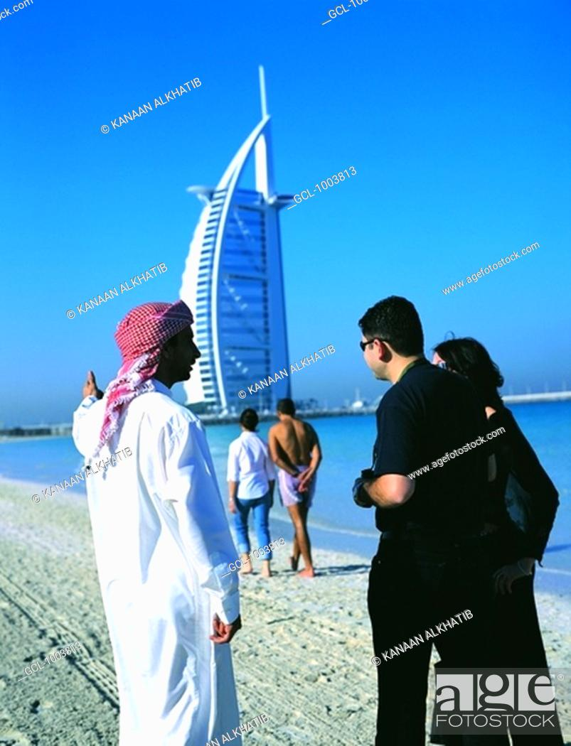 Stock Photo: Arab man shows Burj Al Arab hotel to western couple, Dubai, UAE.