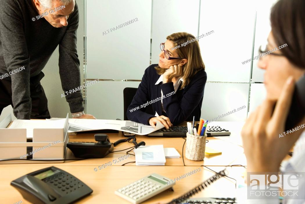 Stock Photo: Colleagues working together in office.