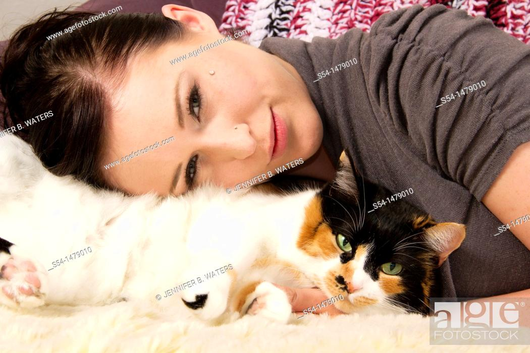 Stock Photo: A young caucasian woman and her calico cat indoors.