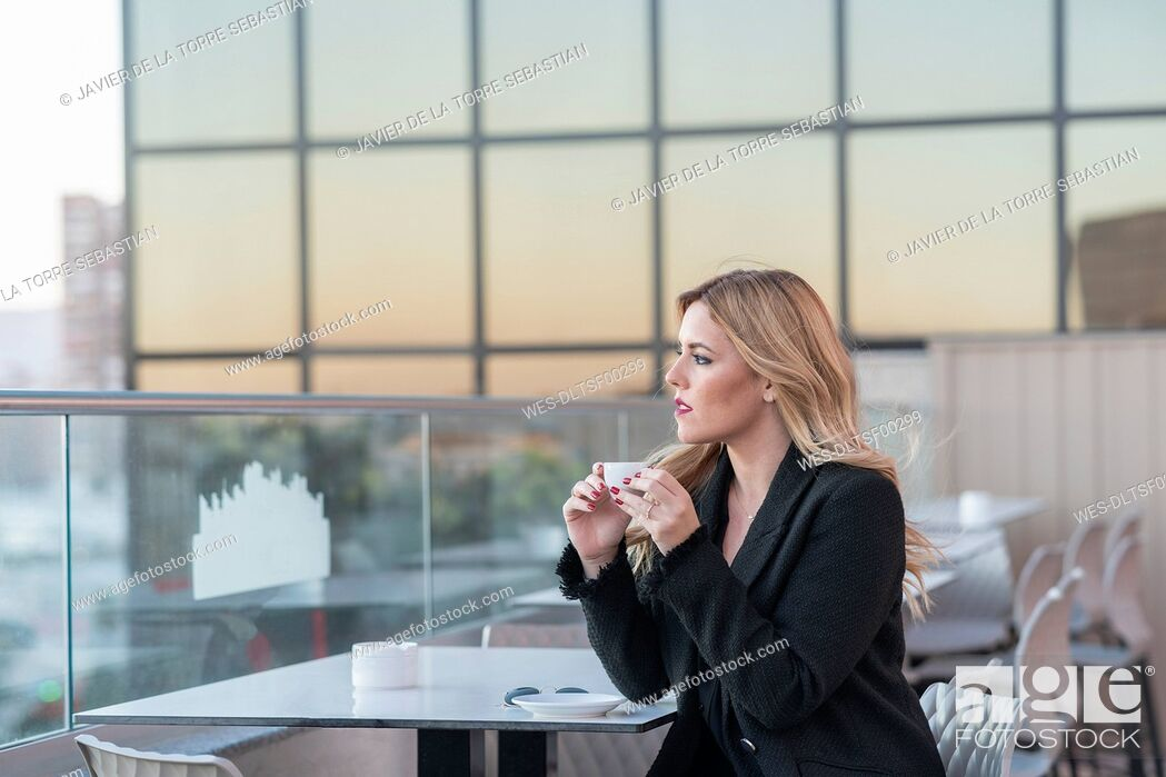 Stock Photo: Businesswoman after work taking a coffee.