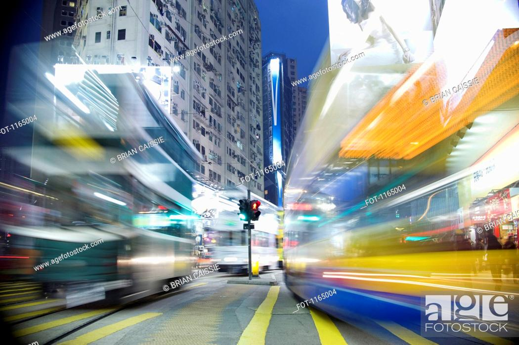 Stock Photo: Buses moving through a city at night, blurred motion.