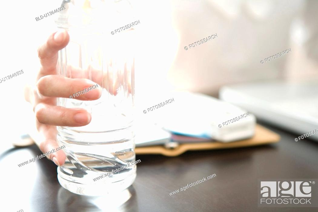Stock Photo: Hand gripping a bottle of water.