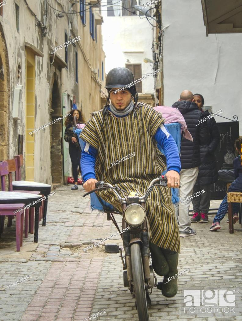 Stock Photo: young man in traditional dress on a moped, Essaouira, Morocco.