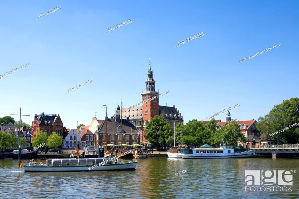 Stock Photo: Passenger boats in river with city hall in background, Leer, Lower Saxony, Germany.