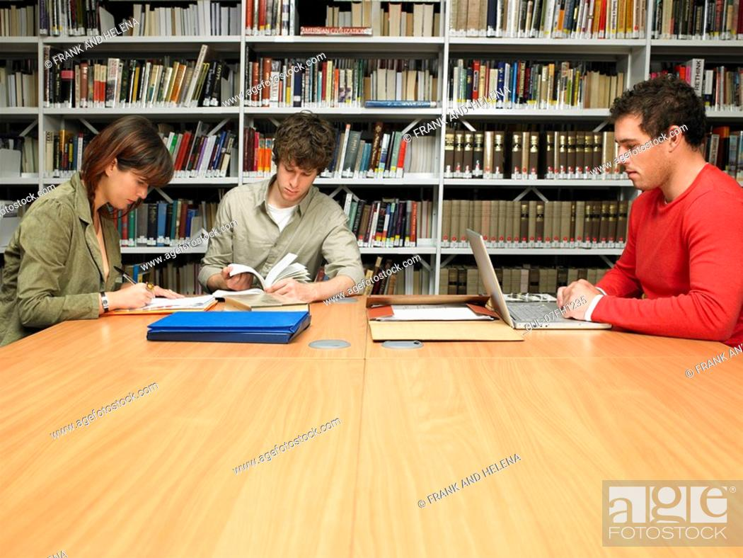 Stock Photo: Young people studying in library.