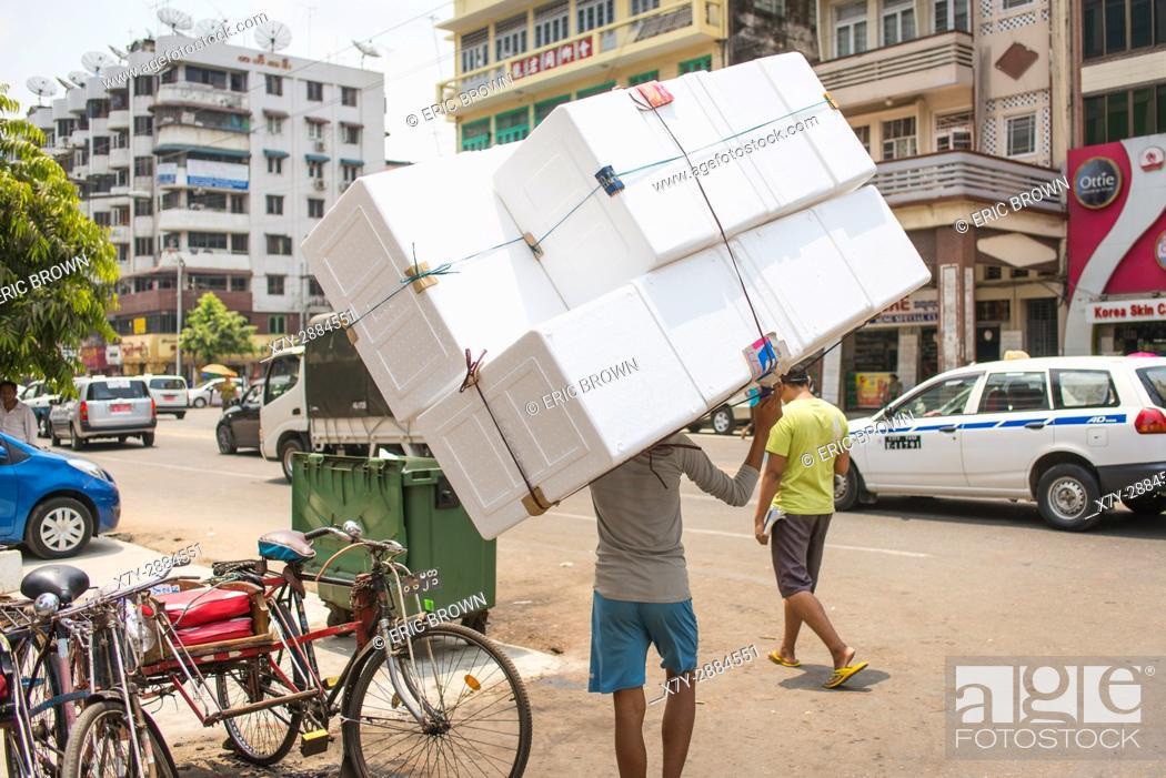 Stock Photo: A young man carrying a big thing. Lanmadaw Township, Yangon, Myanmar.