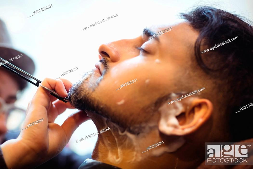 Stock Photo: Man getting his beard shaved with razor.