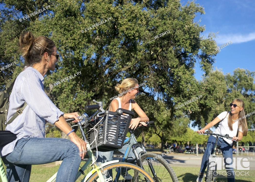Photo de stock: Group of friends enjoying an afternoon on bicycles in the park....