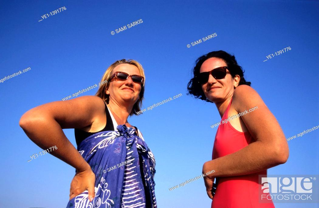 Stock Photo: Two women standing against a blue summer sky in their swimsuits.