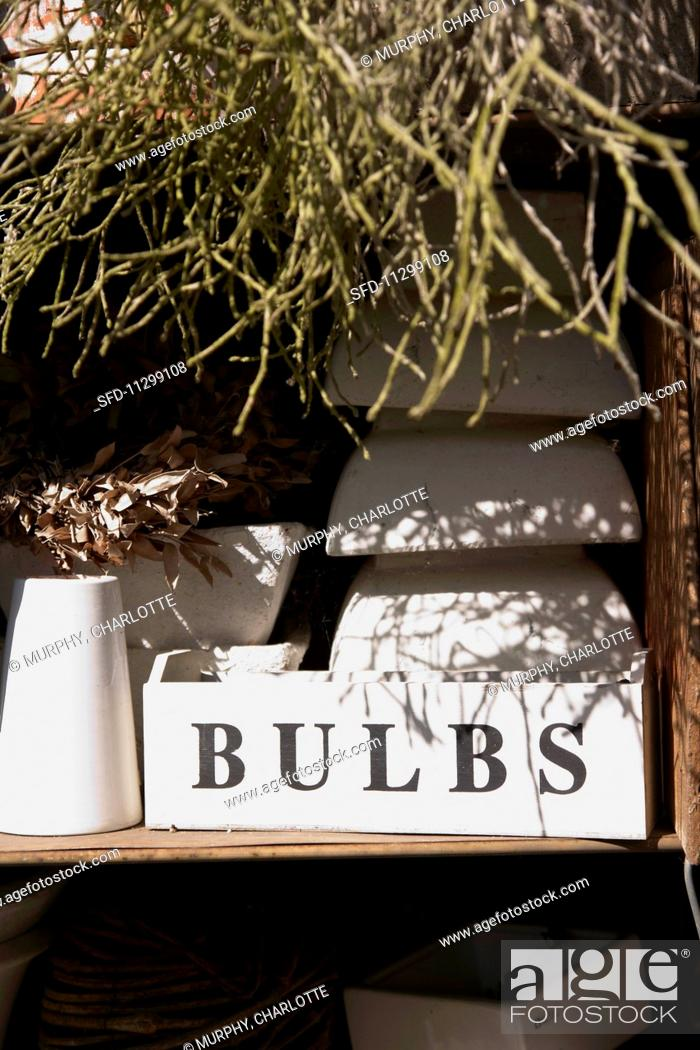 Stock Photo: Stacks of plant pots on a shelf behind a white box with a label.