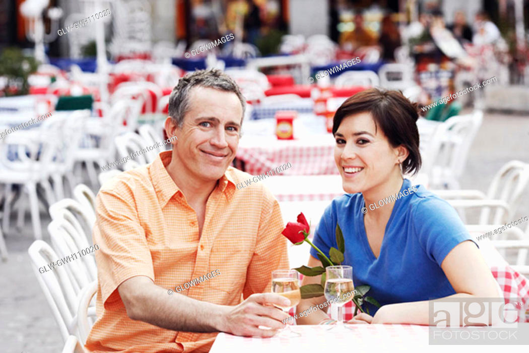 Stock Photo: Portrait of a mature man and a young woman sitting together at a sidewalk cafe.