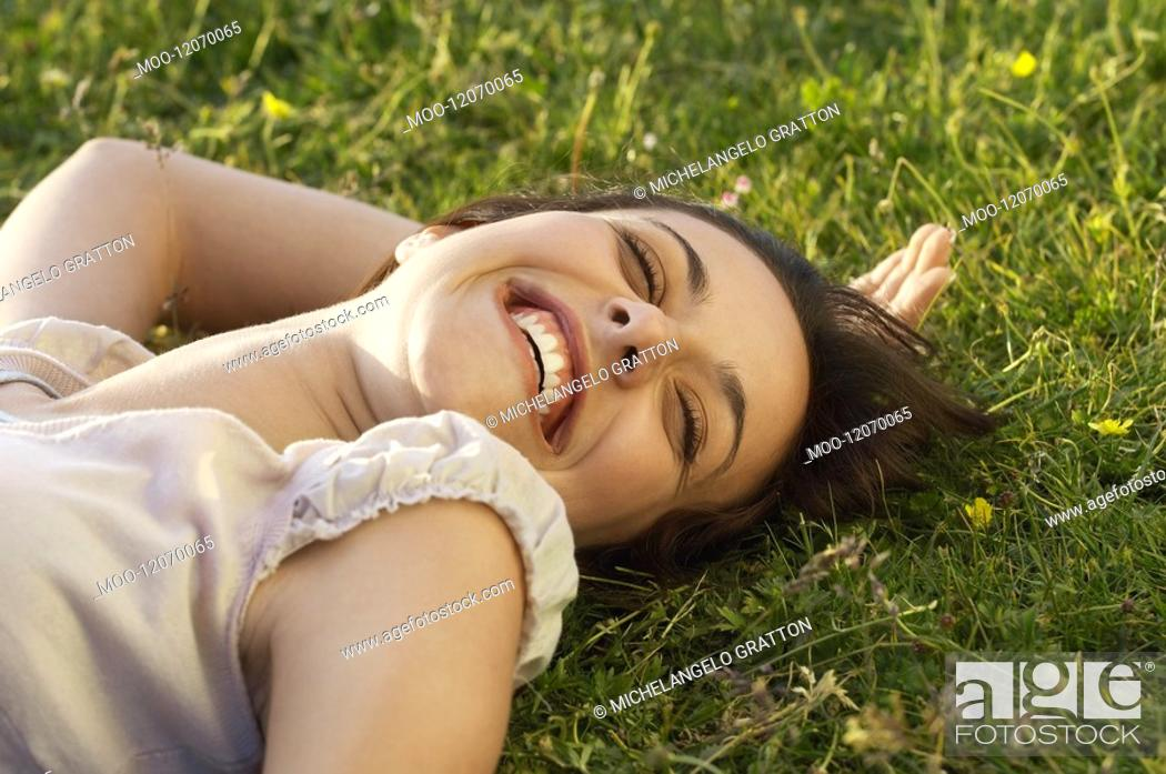 Stock Photo: Smiling young woman lying on grass close up.