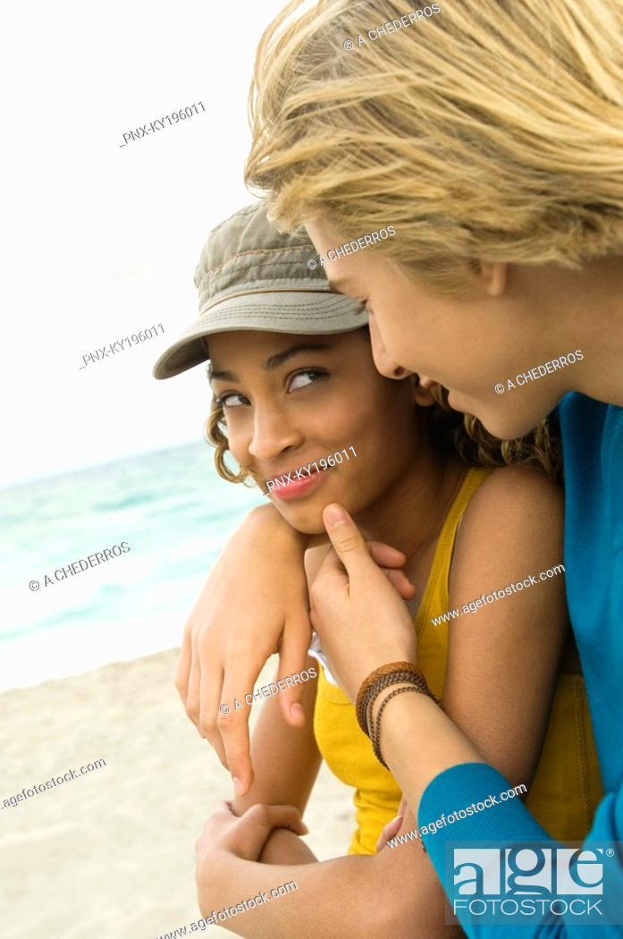 Stock Photo: Teenage boy with a girl romancing on the beach.