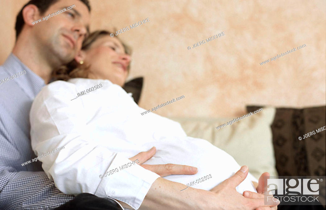 Stock Photo: A young couple, young man and young pregnant woman, 25-30 30-35 35-40 years old, sitting on the sofa.
