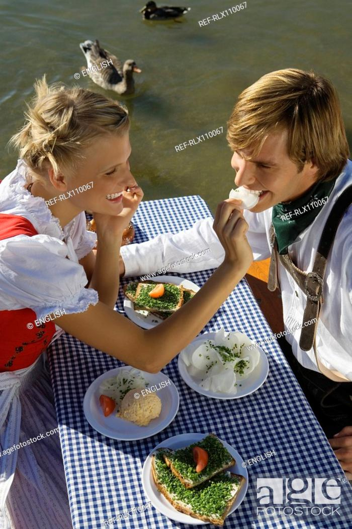 Stock Photo: Young couple in traditional Bavarian outfit, eating meal in beer garden, Munich.
