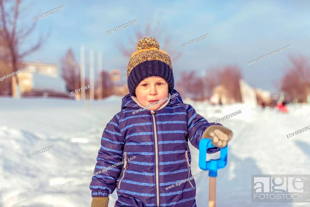 Stock Photo: A little boy in the winter in the city, in a blue jumpsuit and a warm yellow hat. In the hands of holding a spatula. Surprised resting in nature outside the.