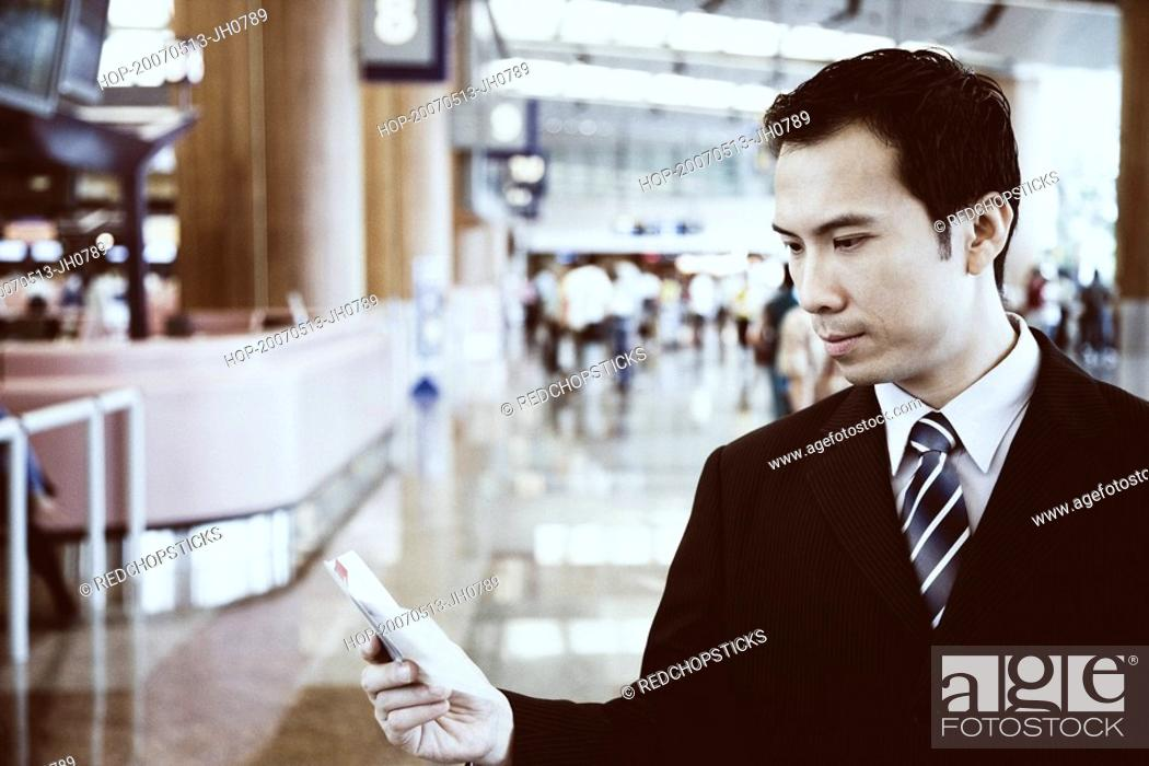Stock Photo: Close-up of a businessman holding a pocket diary at an airport.