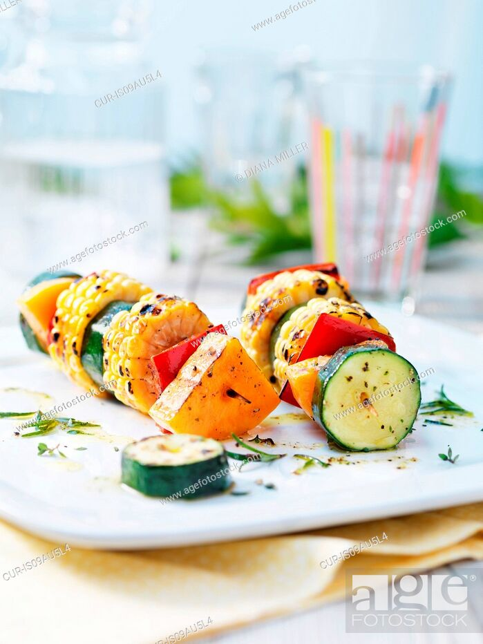 Imagen: Vegetarian kebabs with courgettes, sweet corn on the cob, red pepper, butternut squash and drizzled olive oil.