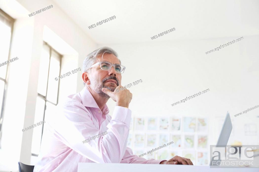 Stock Photo: Portrait of pensive businessman with laptop at his desk in an office.