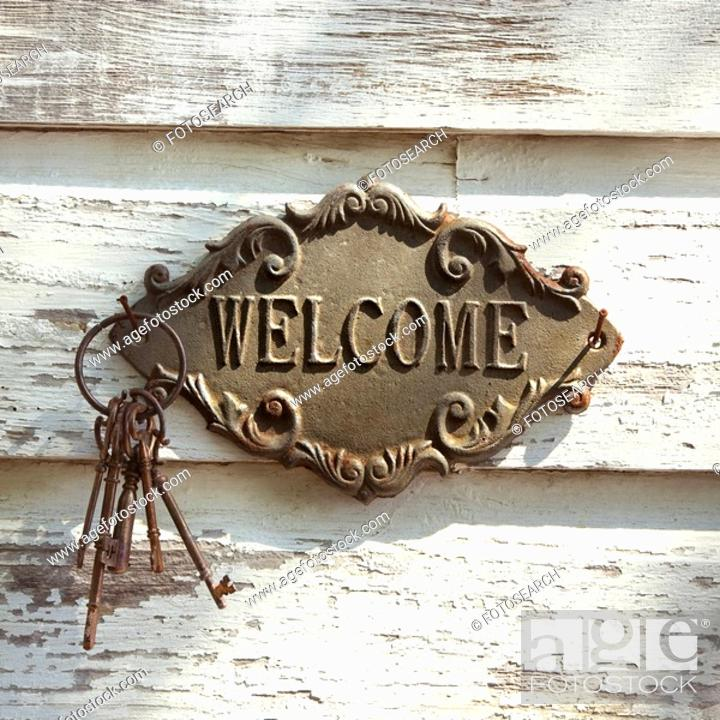 Stock Photo: Welcome sign and metal keys on old white peeling building.