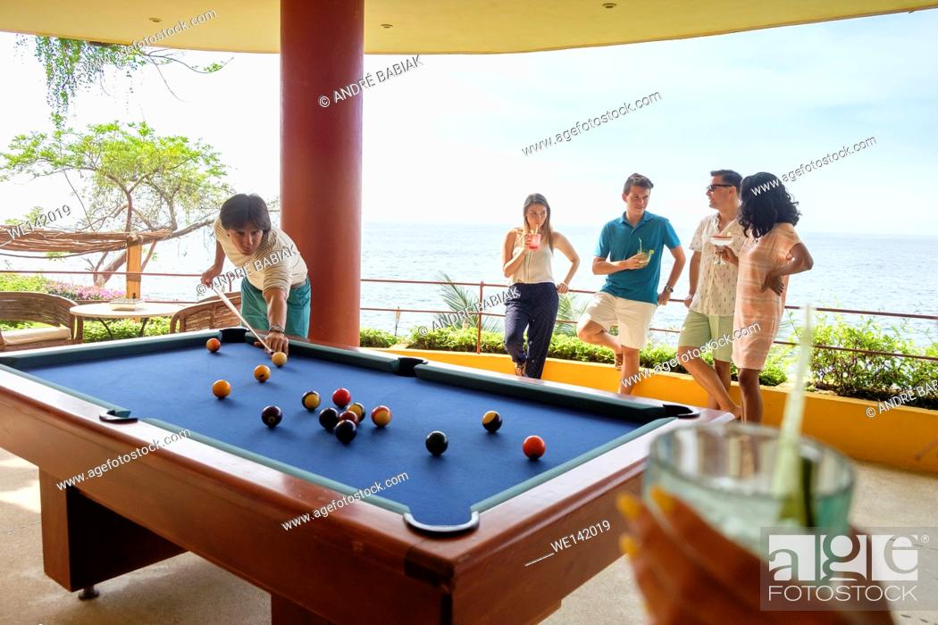 Stock Photo: People having cocktail drinks while playing pool billiard on the terrace of an ocean front villa in Mexico.