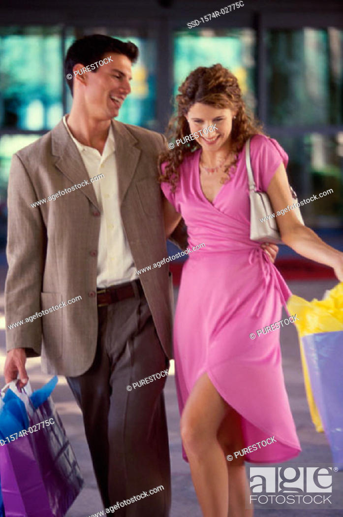 Stock Photo: Young couple carrying shopping bags.