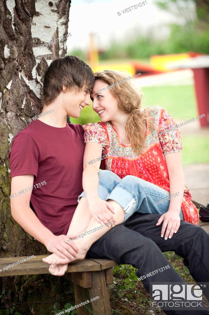 Stock Photo: Germany, Bavaria, Ammersee, Young couple on bench, outdoors, portrait.