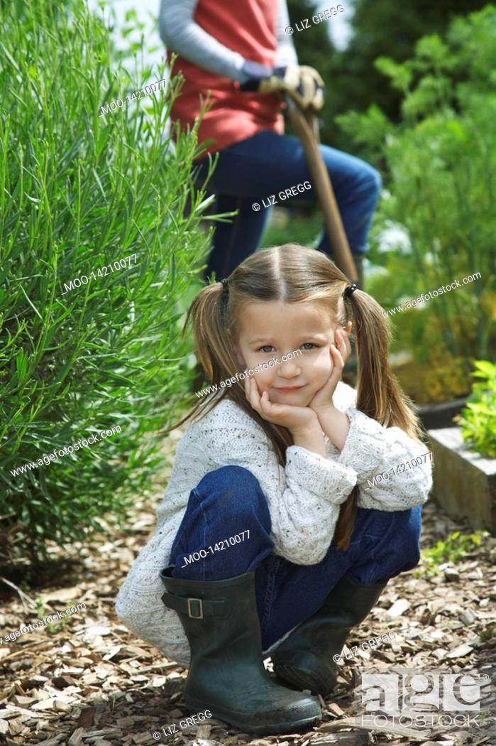 Stock Photo: Girl 5-6 in garden with mother mid section portrait.