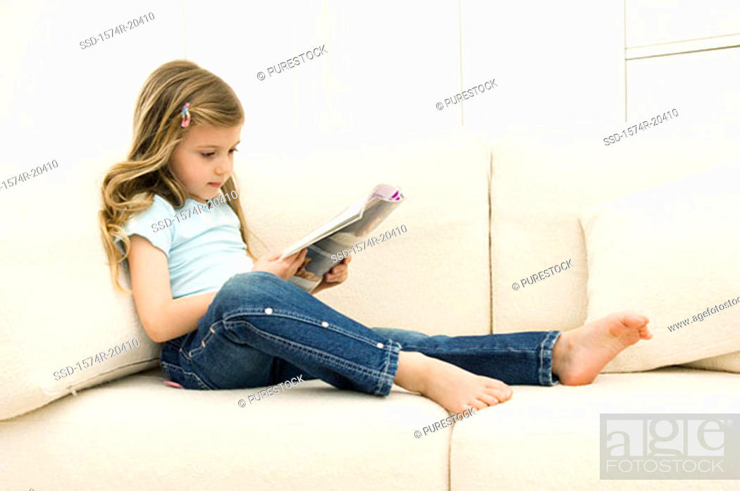 Stock Photo: Girl reading a magazine on a couch.