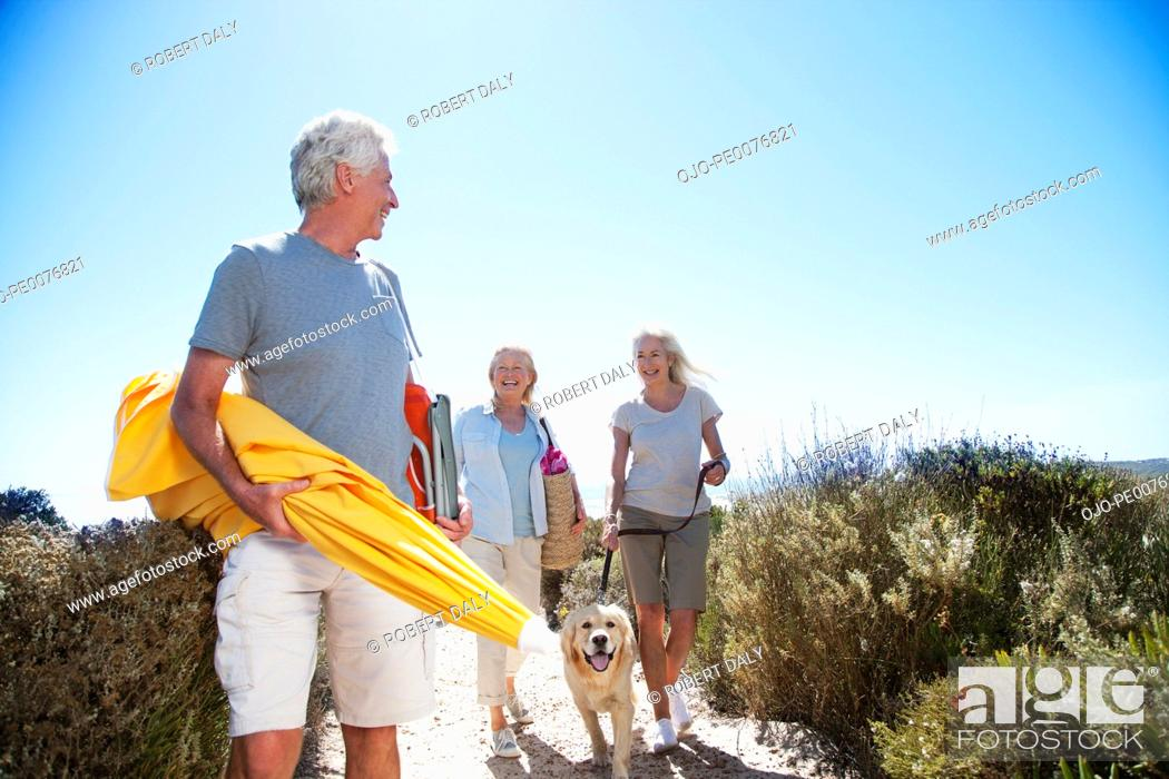 Stock Photo: Senior friends with dog walking on beach path.