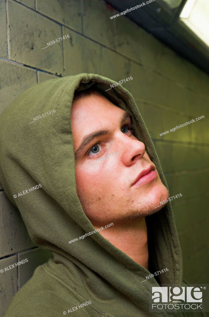 Stock Photo: Young man in hooded sweat top seems bored and disaffected.