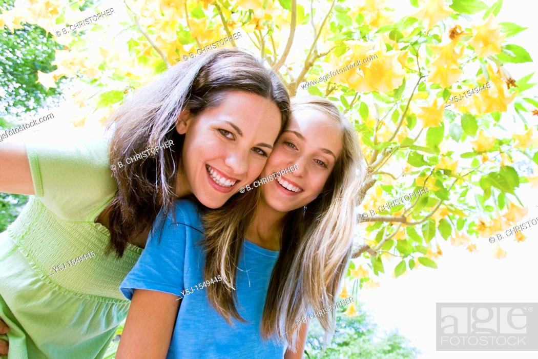 Stock Photo: Young mother and teenaged daughter smiling happily under a flowering tree.