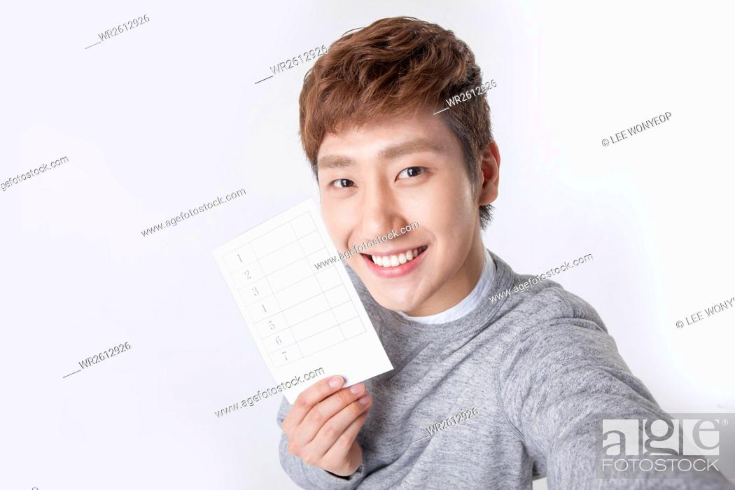 Imagen: Portrait of young smiling man posing with a ballot.
