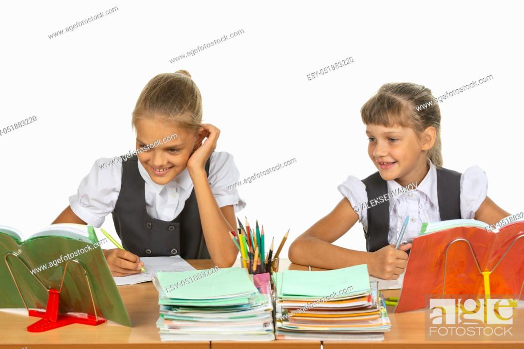 Stock Photo: Two schoolgirls are sitting at a desk and cheerfully looking at the textbook.