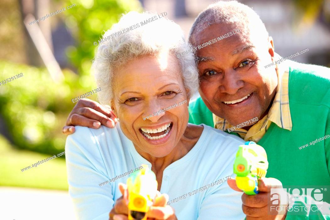 Stock Photo: Senior Couple Shooting Water Pistols.