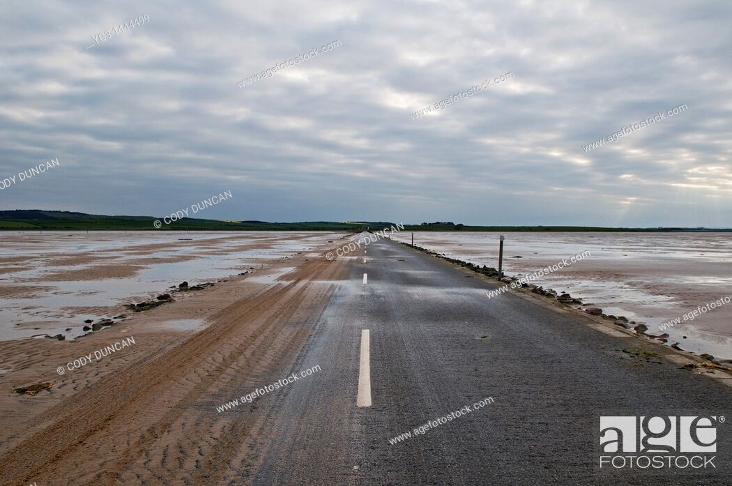 Stock Photo: Sand covered road to Lindisfarne - Holy island at low tide, Lindisfarne, England  The road is only passable for a few hours around low tide.