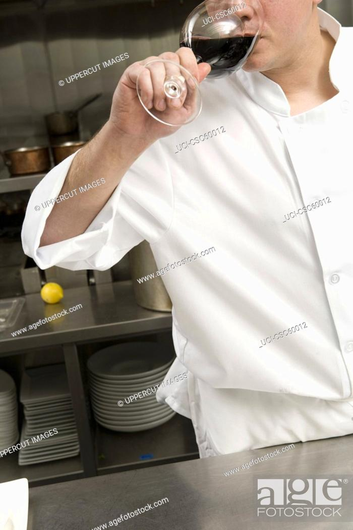 Stock Photo: Male chef drinking glass of wine.