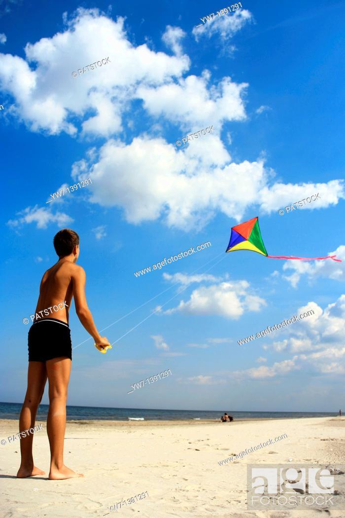 Stock Photo: A teen boy flying his kite at a beach.