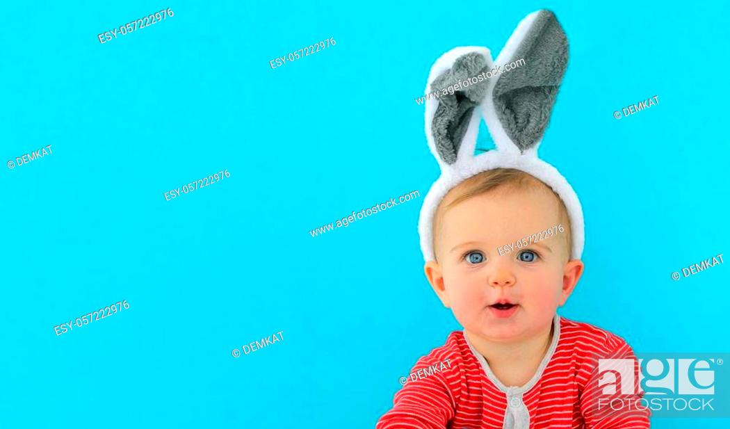 Stock Photo: Portrait of a cute little child girl with bunny ears on a blue background.