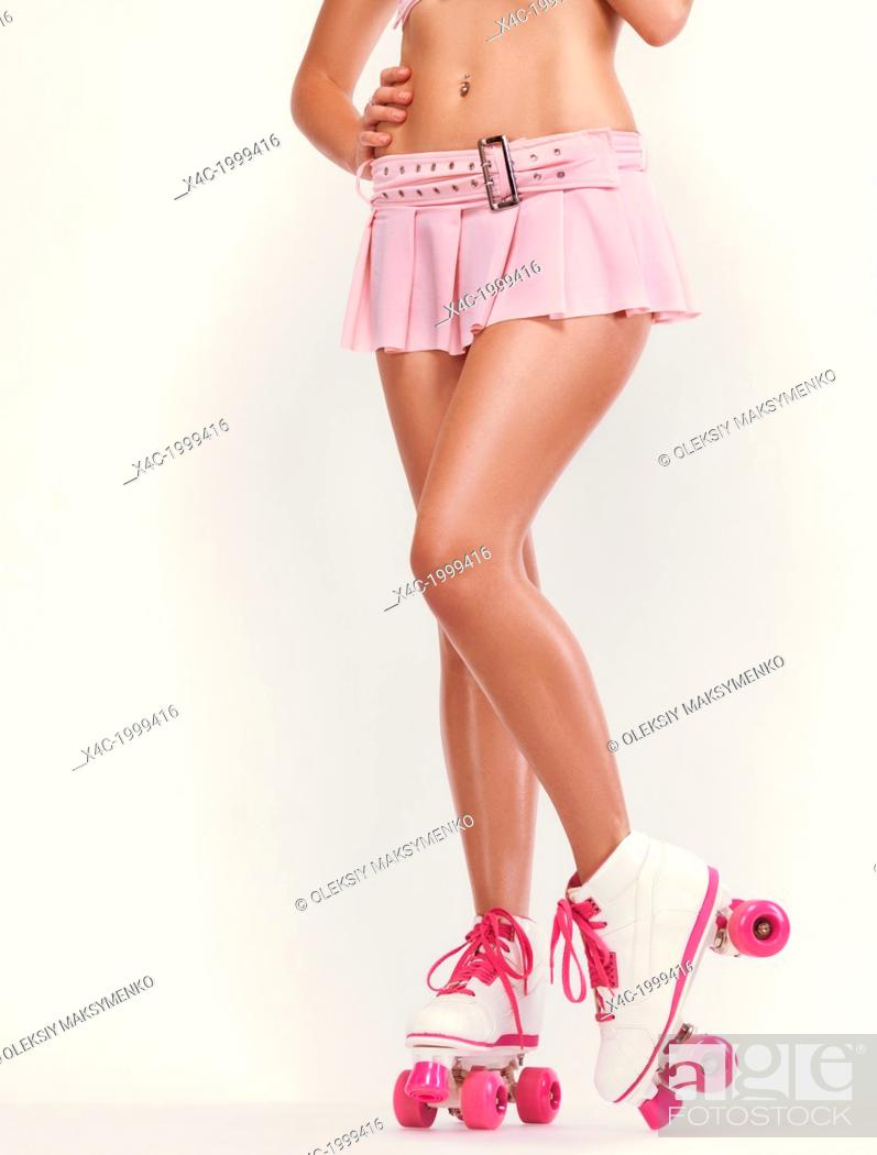 29f753122 Stock Photo - Sexy young woman wearing a pink mini skirt and classic retro  roller skates isolated on off white background.
