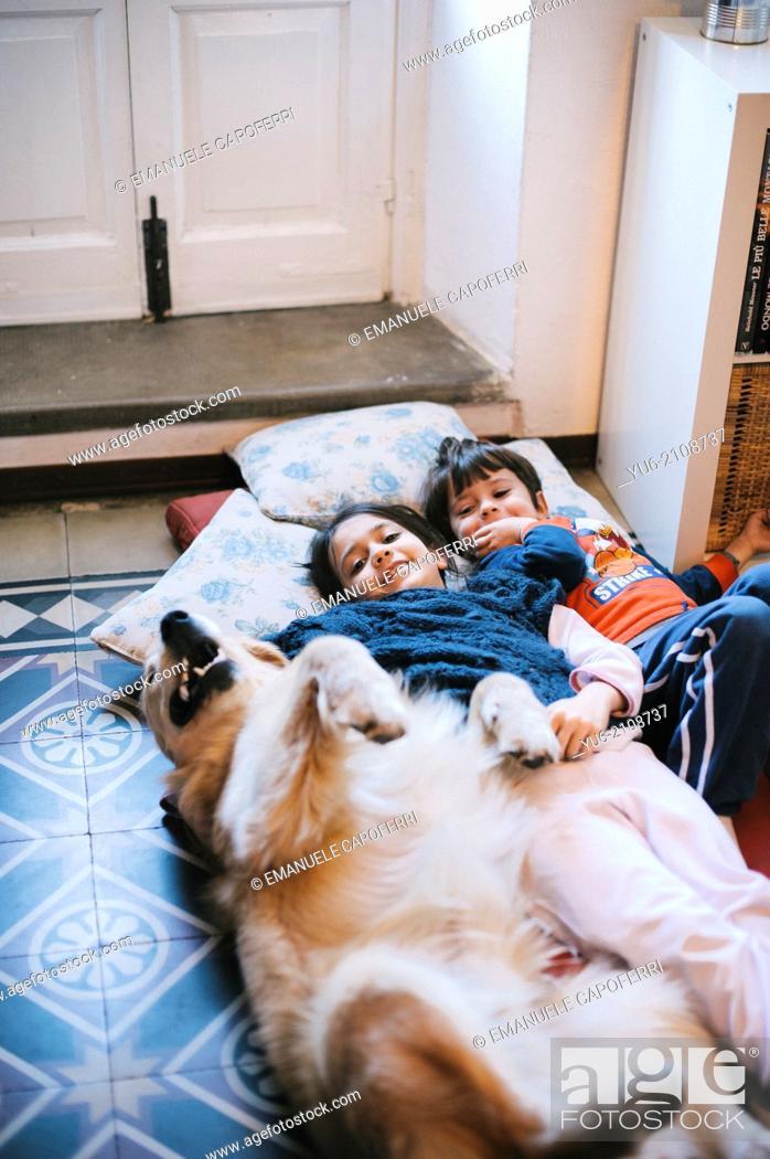 Stock Photo: Children lying on the floor with their golden retriever dog.