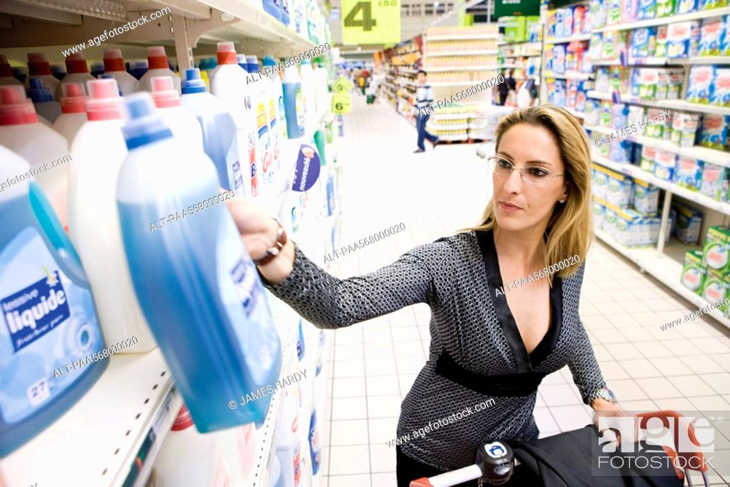Stock Photo: Woman selecting bottle of detergent from supermarket shelf.