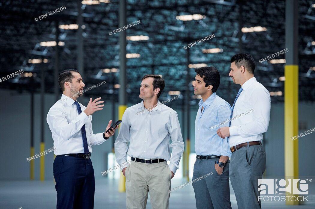 Stock Photo: Businessmen talking in empty warehouse.