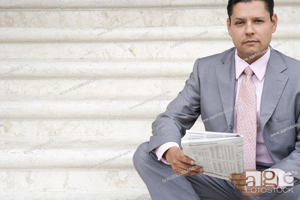 Stock Photo: Businessman reading a newspaper.