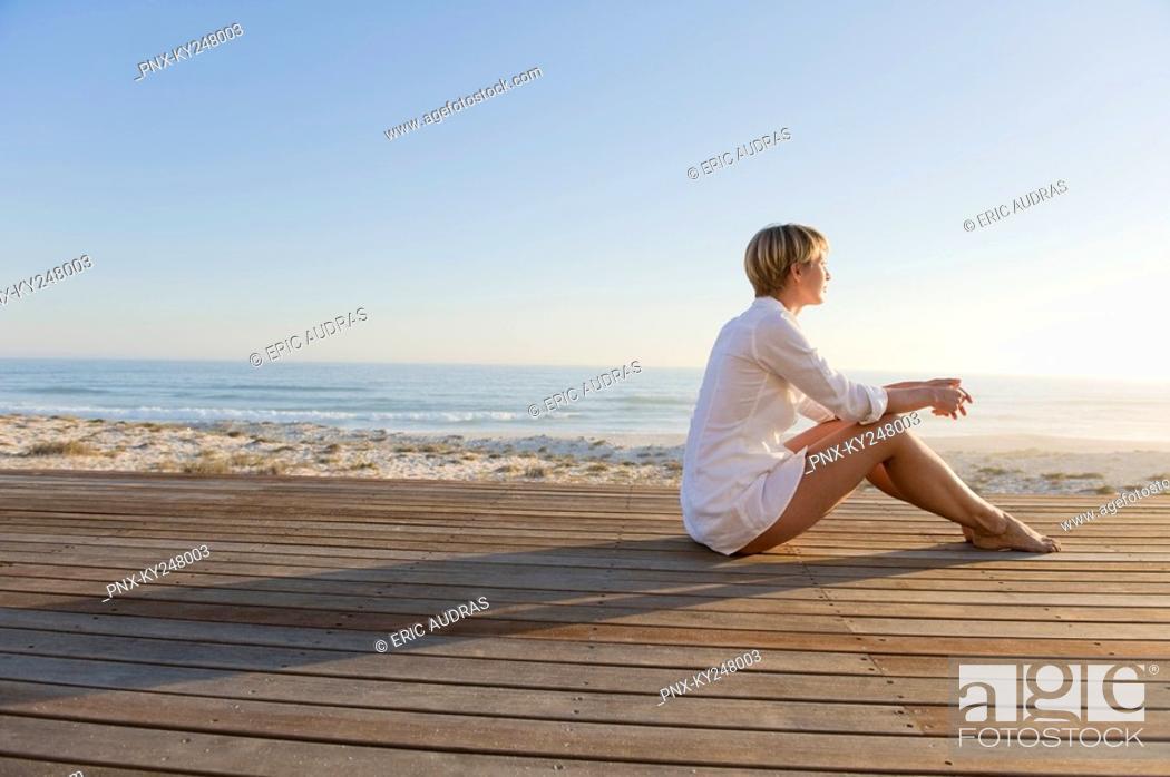 Stock Photo: Woman sitting on a boardwalk.